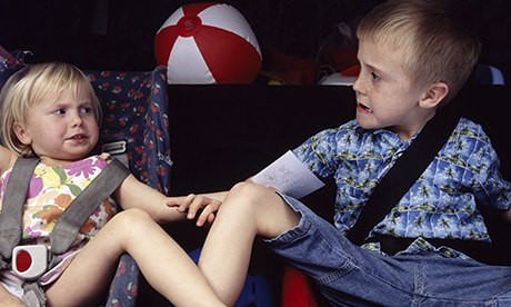 Two children fighting in the backseat of a car